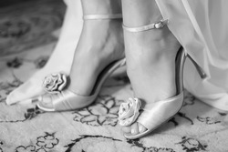 Bride wearing grey silver high heel strap shoes with decorative rose and open toes on carpet in black and white