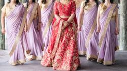 Bride wearing red lehnga with bridesmaids wearing purple sari wedding day