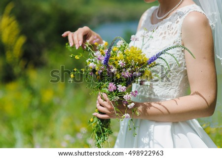 Bride with a bouquet of wildflowers #498922963