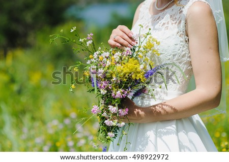 Bride with a bouquet of wildflowers #498922972