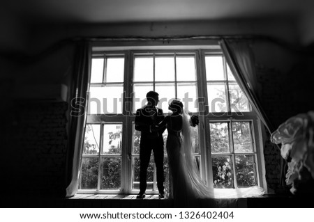 bride with a long veil and a stylish groom in a suit posing on their wedding day on the window #1326402404