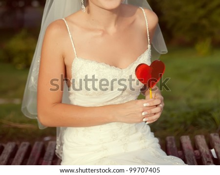 bride with a red heart in hands - stock photo