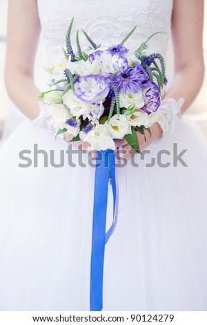 Bride with a wedding bouquet with white and violet flowers tied with blue ribbon, soft focus.