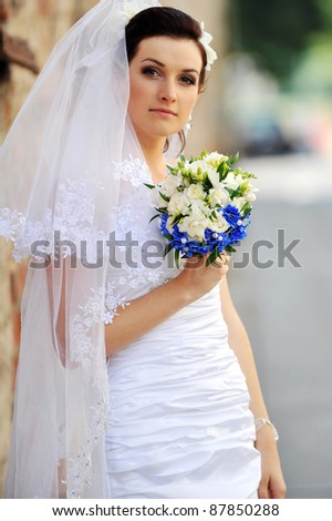 bride with flowers near an old brick wall