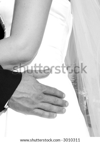 Bride with groom holding onto waist in black and white