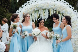 Bride with her friends in blue dresses with bouquets of flowers. Outgoing ceremony. Style. Fashion. Wedding.