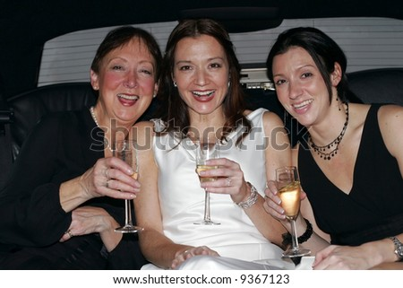 bride with mother and sister in limo drinking champagne
