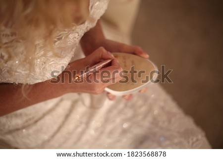 Bride writes under shoe wedding ritual superstition . hand of a bride writing single friends name under her shoe before wedding . Bride writing her shoe with a pencil . Foto stock ©