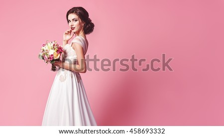 Bride.Young fashion model with perfect skin and make up, beige background, curly hair, flowers in hair