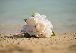 Brides bouquest bunch of flowers posy on sandy tropical beach romanitc concept
