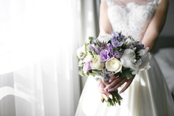 Brides wedding bouquet with peonies, freesia and other flowers in women's hands. Light and lilac spring color. Morning in room