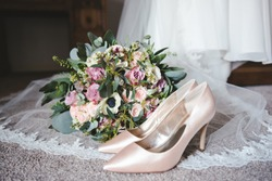 Brides wedding shoes and vintage style bouquet of flowers resting on a lace veil