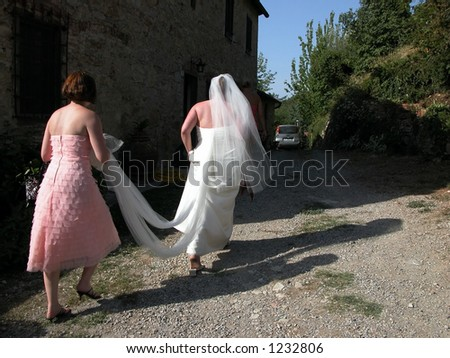 bridesmaid carrying train behind bride walking uphill outdoors