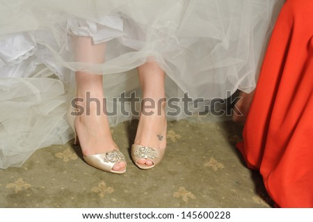 bridesmaid helping bride to put on wedding shoes