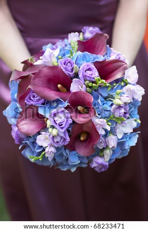 stock photo Bridesmaid holding blue and purple wedding bouquet against