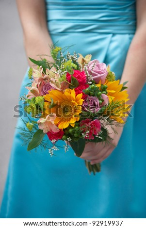 Bridesmaid holding colorful wedding bouquet against blue dress