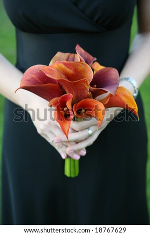 Bridesmaid holding colorful wedding bouquet against dress