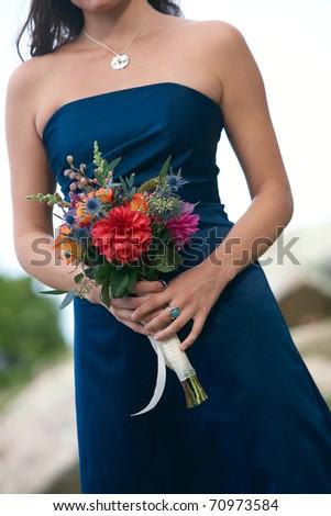 Bridesmaid holding wedding bouquet against blue dress