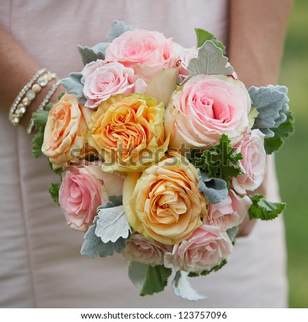 Bridesmaid holding wedding bouquet of roses