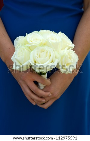 bridesmaid in blue dress holding a white rose wedding bouquet
