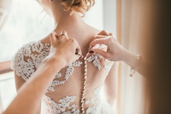 Bridesmaid preparing bride for the wedding day, helping fasten her dress