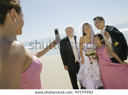 Bridesmaid Taking Picture of Newlyweds and Family