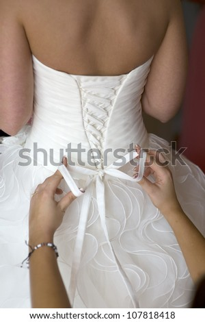 bridesmaid tying the dress for the bride on her wedding day