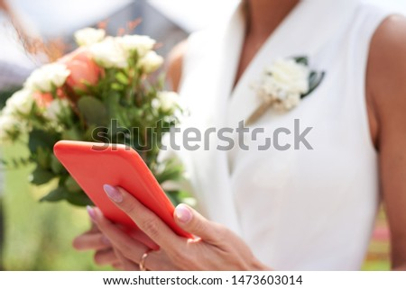 Bridesmaid, wearing white dress, holding flowers and living coral orange phone, taking picture. Close-up picture of hand with phone. Wedding day.