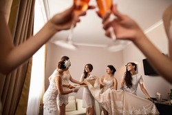 Bridesmaids having fun with bride. Wedding preparation. Russian translation of the inscription