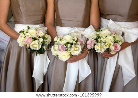 bridesmaids holding bouquet of flowers at a wedding