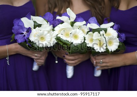 bridesmaids holding bouquets of white gerbera, white lilies and purple orchids