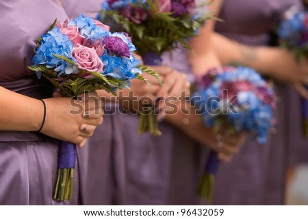 Bridesmaids holding colorful bouquets at wedding ceremony