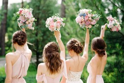 Bridesmaids in pink dresses and bride holding beautiful bouquets. Beautiful luxury wedding blog concept. Summer wedding.