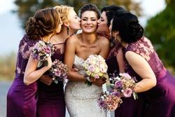 Bridesmaids kiss beautiful bride standing outside