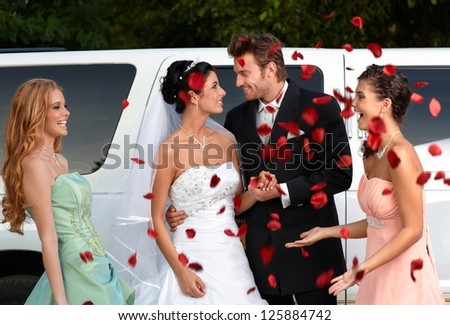 Bridesmaids throwing rose petals on young couple.