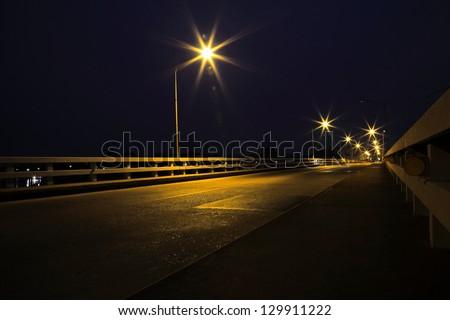 Bridge across the river at night in Ubon Ratchathani, Thailand.(Mun River)