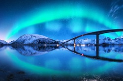 Bridge and aurora borealis over snowy mountains. Lofoten islands, Norway. Amazing northern lights and reflection in water. Winter landscape with starry sky, polar lights, road, sea, city illumination