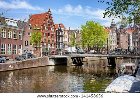 Bridge and traditional Dutch houses on Oudezijds Voorburgwal canal, city of Amsterdam, Netherlands.
