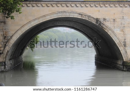 Bridge arch over river in misty day