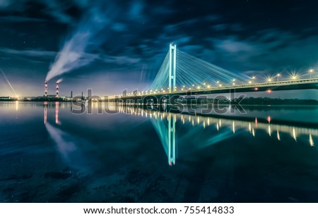 Bridge at sunset across the Dnieper River. Kiev bridge against the backdrop of a beautiful sunset in Kiev. Bridge in evening sunshine.