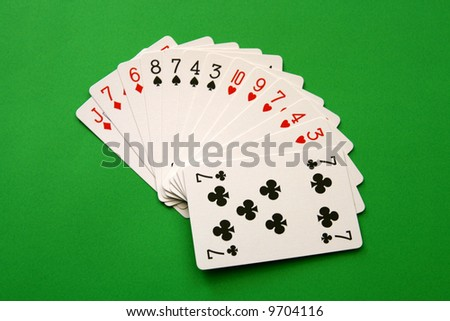 bridge cards - one hand (8,7,4,3 spades, 10,9,7,4,3 hearts, J,7,6 diamonds, 7 club)  background green,