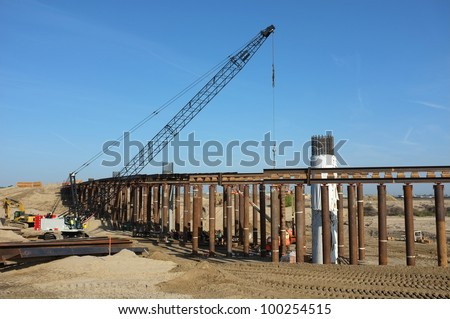 Bridge Construction Project: Reinforced concrete columns and temporary wood and steel shoring are in place as crane lifts structural steel beams to position