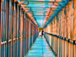 Bridge crossing, pedestrian overpass made of metal structures over the river along the railway. A good example of regularity (monotony) and one-point perspective. Blurred people