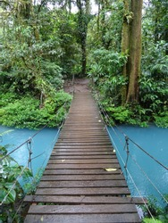 Bridge crossing the turquoise waters of the Rio Celeste at the heart of Costa Rica tropical rainforest
