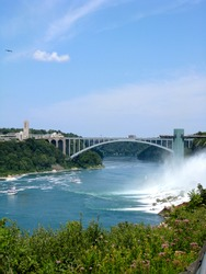 Bridge crossing to Canada side of Niagara Falls in summer. Crashing water with boat on the river. Green lush plants and a bright blue sky