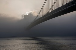 Bridge hidden in the fog at sunrise. The Verrazano-Narrows Bridge is a double-decked suspension bridge that connects the New York City boroughs of Staten Island and Brooklyn