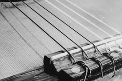Bridge of an acoustic guitar. Nylon strings tied on the guitar bridge. Depth of field, details of an old acoustic guitar, worn out and dusty. Black and white macro photo.