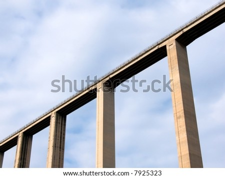 Bridge of cement on the background of a blue sky with cloud