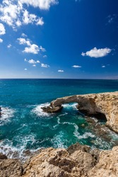 Bridge of Lovers or Monk seal arch, stone cliffs in the Mediterranean sea in Ayia Napa, Cyprus. Vertical frame.