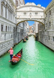 Bridge of Sighs (Ponte dei Sospiri) and row of gondolas with gondoliers and Rio de Palazzo o de Canonica Canal from Riva degli Schiavoni in Venice, Italy. Ponte de la Canonica is visible in background